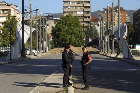 Hungarian NATO peacekeepers patrol on the main bridge of the ethnically divided town of Mitrovica
